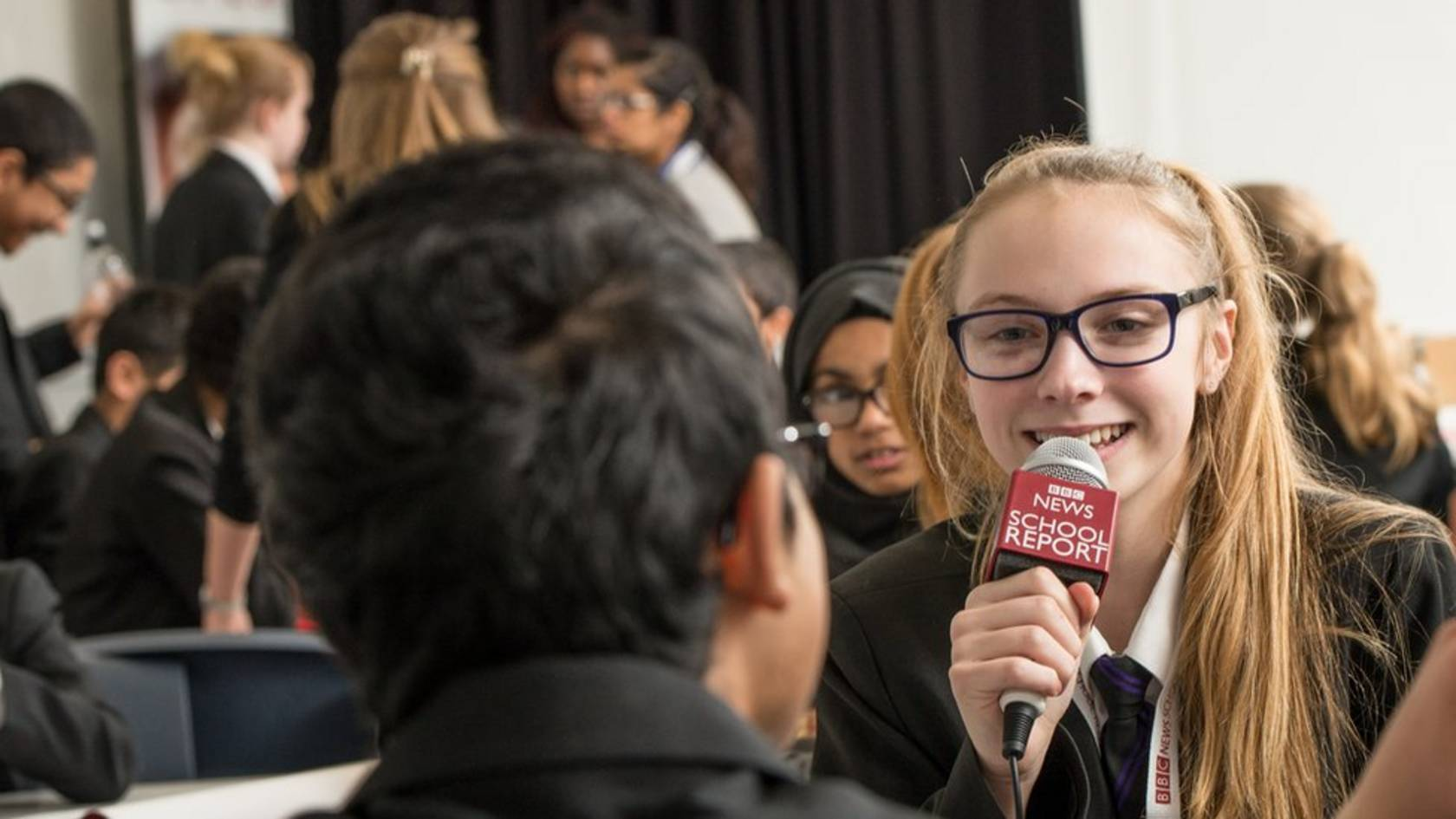 Female student with School Report microphone surrounded by other young people