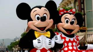 Mickey and Minnie Mouse walk around the Main Street of Hong Kong Disneyland during a preview of the park