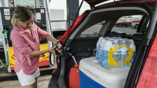 Jennifer Tate fuels up a gas can next to bottled water an other supplies as she prepares for the arrival of Hurricane Ida in Pass Christian, Mississippi, USA, on 27 August 2021
