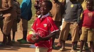 A young boy in Rwanda playing rugby