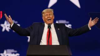 Former President Donald Trump gestures with open arms at a conference in February