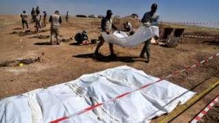 આઈએસ દ્વાર માર્યા ગયેલા 123 લોકોના અવશેષો તેમની ઓળખ માટે એક સામૂહિક કબરમાંથી ખોદાઈ રહ્યા છે