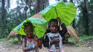 Children holding leaves to protect themselves from the rain pose in Boffa, Guinea - Sunday 25 July 2021