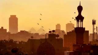 Prédios e construções antigas ao entardecer no Cairo, de onde se vê ao fundo duas pirâmides