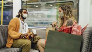 Mand and woman wear masks on Metro