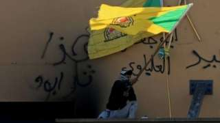 Man waves a Kataib Hezbollah flag outside US embassy in Baghdad (file photo)