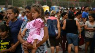 A female migrant holds her young daughter at makeshift camp in Mexico