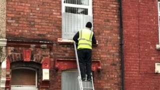 A council worker boarding up the house