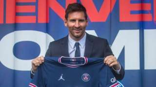 Lionel Messi holds his new Paris St-Germain jersey