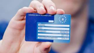 A hand holding a European Health Insurance Card