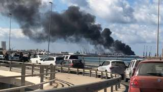 Smoke rises from the port in Tripoli after being attacked in Libya, 18 February 2020