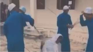 Screenshot from the video showing two pupils receive severe beatings. One student is kneeling. The other is lying flat on the ground.