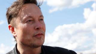 Elon Musk looks into the middle distance in a close-up against a blue sky