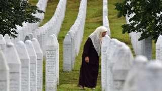 A Srebrenica survivor kisses her son's gravestone