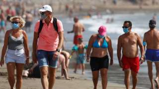 Several people walk along the beach wearing face masks in Playa del Ingles, Gran Canaria, Spain, August 14, 2020.
