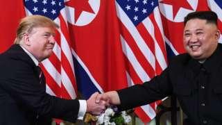 US President Donald Trump (L) shakes hands with North Korea's leader Kim Jong Un
