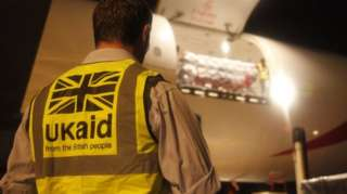 UK aid worker in front of a plane