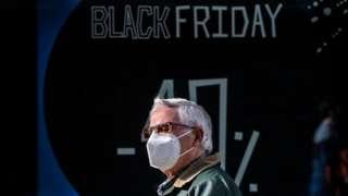Homem usando máscara passa diante de vitrine que anuncia desconto da Black Friday