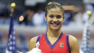 """Great Britain""""s Emma Raducanu holds the trphy as she celebrates winning the women""""s singles final on day twelve of the US Open"""