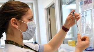 A healthcare worker prepares a dose of a Covid-19 vaccine near Paris
