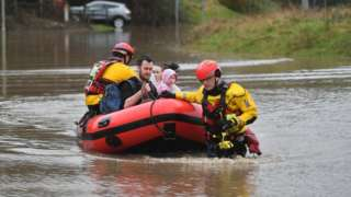 A family in a boat is helped by emergency workers in Nantgarw, Wales