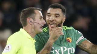 Troy Deeney speaks with referee David Coote