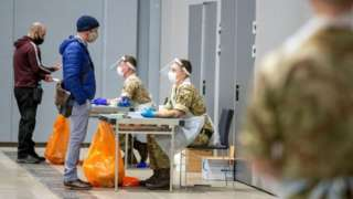 Soldiers talk to people at The Exhibition Centre, in Liverpool, which has been set up as a testing centre as part of the mass coronavirus disease
