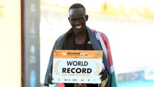 Kibiwott Kandie holding a banner with 'world record' on it