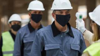 Construction workers having temperatures checked