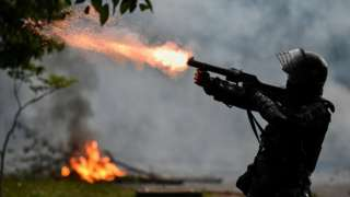 A riot police officer fires tear gas at demonstrators during clashes following a protest against a tax reform bill in Cali, Colombia, 30 April