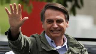 Jair Bolsonaro waves at a polling station