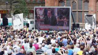 People watch Prime Minister David Cameron on a giant screen making a statement to the House of Commons regarding the findings of the Saville Inquiry into Bloody Sunday, outside the Guildhall in Londonderry.