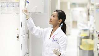 Dr Jingmei Li holds up a test tube in her laboratory.