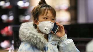 A woman wearing a protective mask uses a smartphone as she shops at a shopping mall in Shenyang in China's northeastern Liaoning province