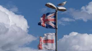 Torn union jack flag and Ulster banner on a lamppost