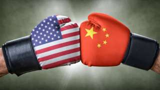 Boxing gloves with the US and Chinese flags clashing