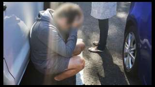 A suspect in custody kneels down and holds his head