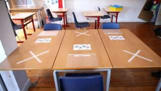 Desks in a school, set up with social distancing in mind