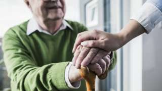 Close-up of woman holding senior man's hand leaning on cane - stock photo