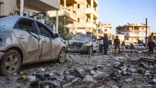 People inspecting bomb damage - shelled-out cars and rubble - in the town Maarat Misrin in Idlib province