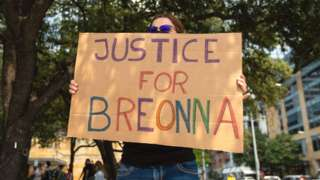 A woman holds a Justice for Breonna sign