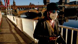 A man wears mask as walks next to Oberbaum Bridge in Berlin, Germany, 2 March 2021
