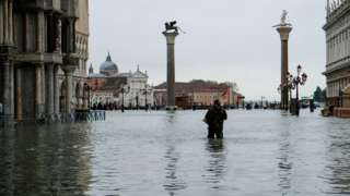 """A man stands in water at the flooded St Mark""""s Square"""