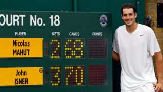 John Isner stands by the scoreboard after he beat Nicolas Mahut 70-68 in the final set at Wimbledon in 2010