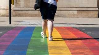 Woman walking over the rainbow crossing in Battersea