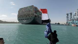 A man waves an Egyptian flag after the Ever Given is fully refloated in the Suez Canal, Egypt (29 March 2021)