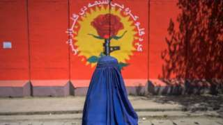 A burqa-clad woman walks past a mural along a street in Kabul on September 15, 2021