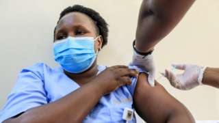 A Kenyan healthcare worker receives vaccinated with an Oxford/AstraZeneca dose