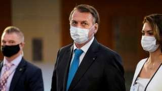 Jair Bolsonaro ao lado da primeira-dama Michele, ambos de máscara e sendo observados por um segurança ao fundo