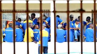 Prisoners are seen at the Makala prison in Kinshasa on December 18, 2012 from behind the bars of the windows of a court room.